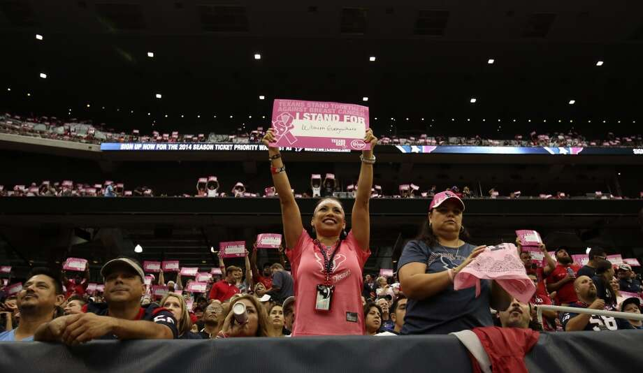Ruth Contreras, of Pearland, holds up a pink breast cancer awareness sign during the second quarter. Photo:  Karen Warren, Houston Chronicle
