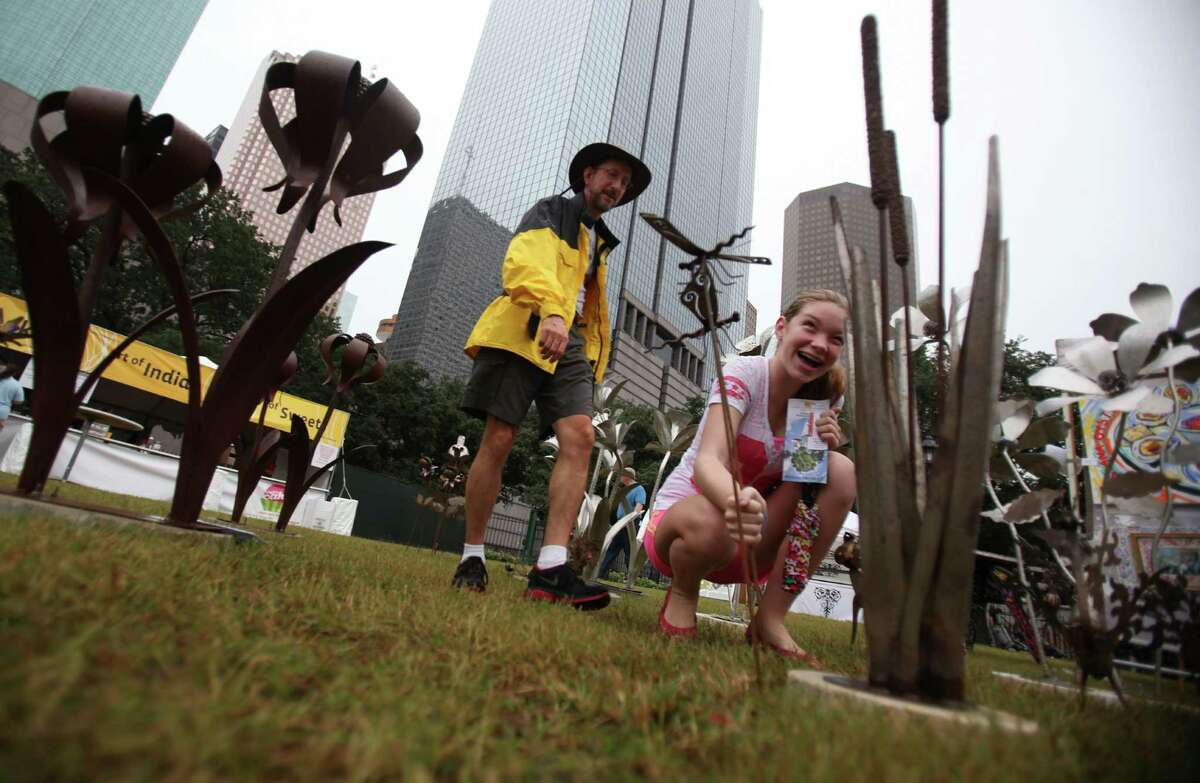 David Watts and daughter Brooke Williams, 12, purchase metal art work by metal sculptor William Colburn at the Bayou City Arts Festival on Sunday, Oct. 13, 2013, in Houston.