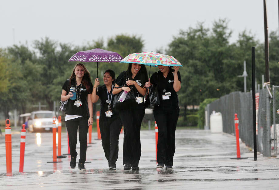Huddled under umbrellas, from left, Lindsey McCloud, Felicia Sanchez, Samantha Guerrero and Brooke Espinoza leave the AT&T Center after the San Antonio Spurs\Phoenix Suns game, Sunday, Oct. 13, 2013. A flash flood warning has been issued for most of South and Central Texas, including San Antonio. Photo: JERRY LARA, San Antonio Express-News / © 2013 San Antonio Express-News