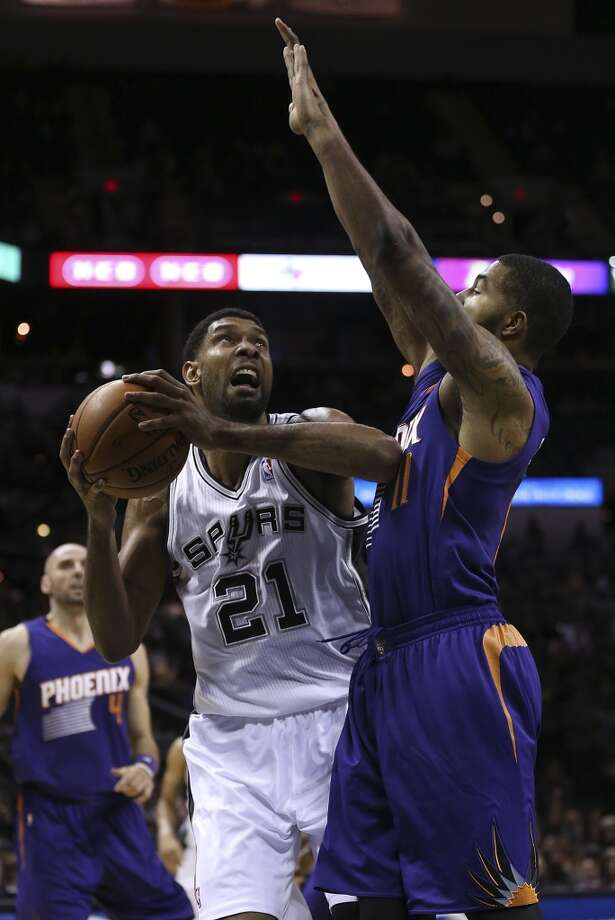 San Antonio Spurs' Tim Duncan looks to shoot over Phoenix Suns' Markieff Morris during the first half at the AT&T Center, Sunday, Oct. 13, 2013. Photo: San Antonio Express-News