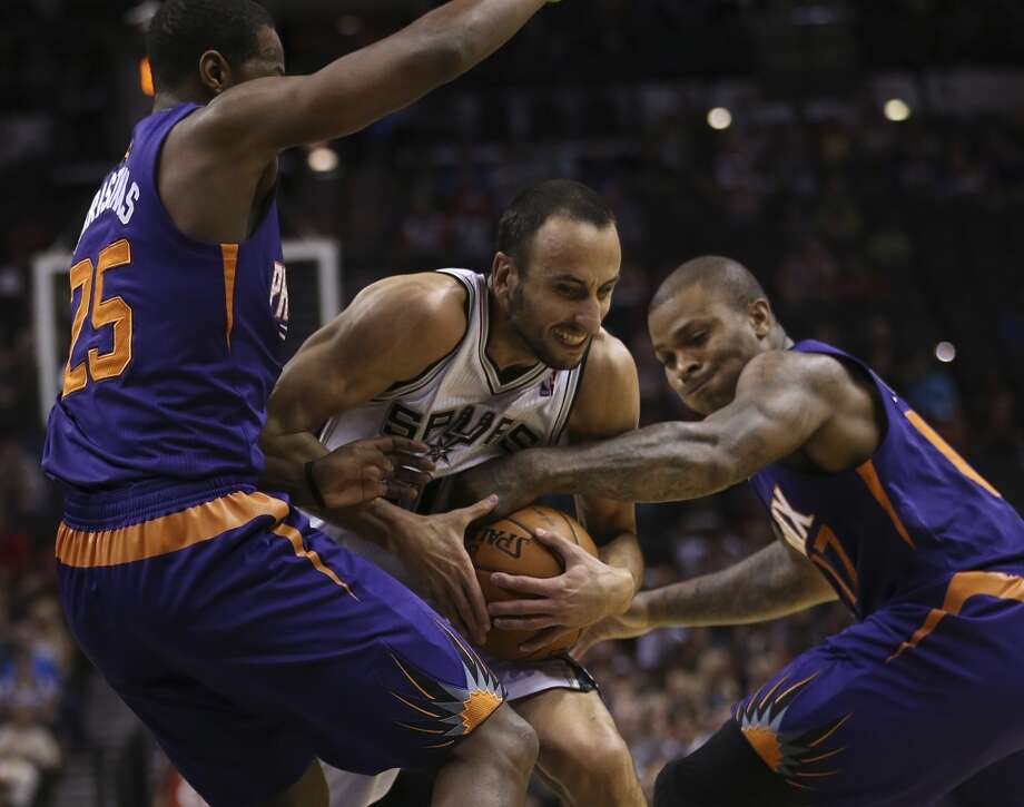 San Antonio Spurs' Manu Ginobili runs into Phoenix Suns' Dionte Christmas, left, and P.J. Tucker during the first half at the AT&T Center, Sunday, Oct. 13, 2013. Photo: San Antonio Express-News