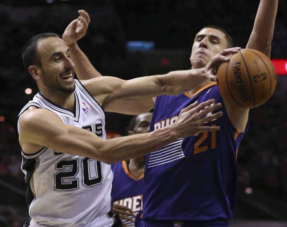 San Antonio Spurs' Manu Ginobili passes the ball under pressure from Phoenix Suns' Alex Len during the first half at the AT&T Center, Sunday, Oct. 13, 2013. Photo: San Antonio Express-News