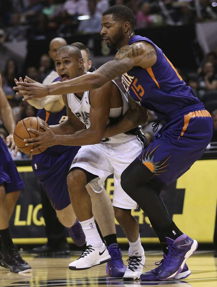 San Antonio Spurs' Patty Mills gets pressure from Phoenix Suns' Marcus Morris during the second half at the AT&T Center, Sunday, Oct. 13, 2013. The Suns won 106-99. Photo: San Antonio Express-News