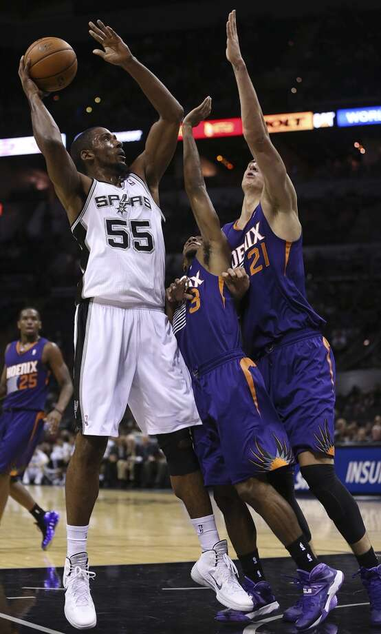 San Antonio Spurs' Marcus Cousin shoots over Phoenix Suns' Ish Smith, center, and Alex Len during the second half at the AT&T Center, Sunday, Oct. 13, 2013. The Suns won 106-99. Photo: San Antonio Express-News