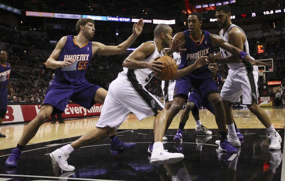 San Antonio Spurs' Tony Parker drives under the basket as Phoenix Suns' Viacheslav Kravtsov, (55), and Channing Frye during the first half at the AT&T Center, Sunday, Oct. 13, 2013. On the right is Tim Duncan. Photo: San Antonio Express-News