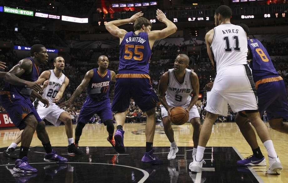 San Antonio Spurs' Tony Parker shoots around Phoenix Suns' Viacheslav Kravtsov during the first half at the AT&T Center, Sunday, Oct. 13, 2013. Photo: San Antonio Express-News