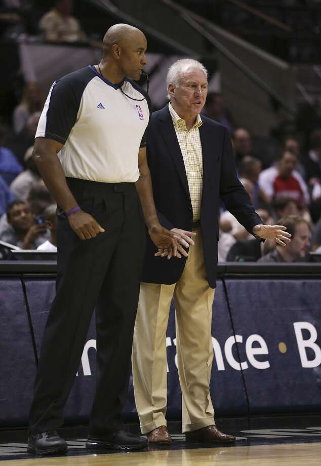 San Antonio Spurs head coach Gregg Popovich talks with official Kevin Cutler during the first half against the Phoenix Suns at the AT&T Center, Sunday, Oct. 13, 2013. Photo: San Antonio Express-News