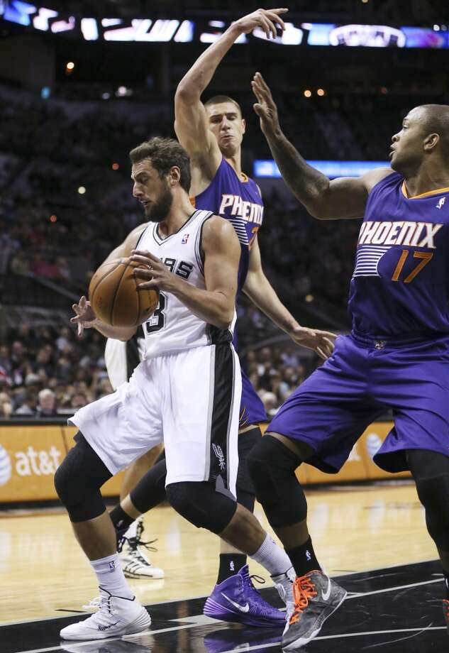 San Antonio Spurs' Marco Belinelli gets a rebound under pressure from Phoenix Suns' Alex Len, back, and P.J. Tucker during the first half at the AT&T Center, Sunday, Oct. 13, 2013. Photo: San Antonio Express-News