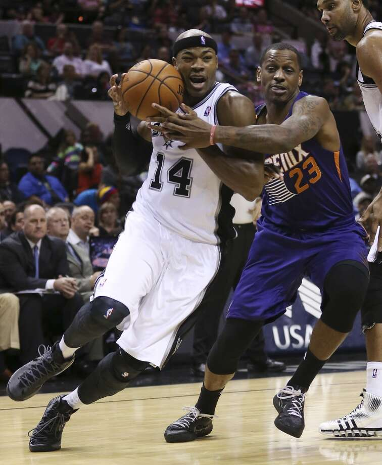 San Antonio Spurs' Corey Maggette drives around Phoenix Suns' James Nunnally during the first half at the AT&T Center, Sunday, Oct. 13, 2013. Photo: San Antonio Express-News