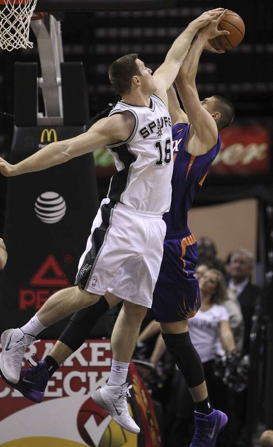 San Antonio Spurs' Aron Baynes blocks a shot by Phoenix Suns' Alex Len during the first half at the AT&T Center, Sunday, Oct. 13, 2013. Photo: San Antonio Express-News