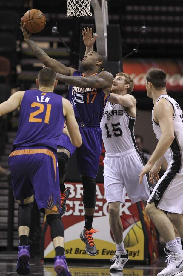 San Antonio Spurs' Matt Bonner tries to stop Phoenix Suns' P.J. Tucker during the first half at the AT&T Center, Sunday, Oct. 13, 2013. Photo: San Antonio Express-News