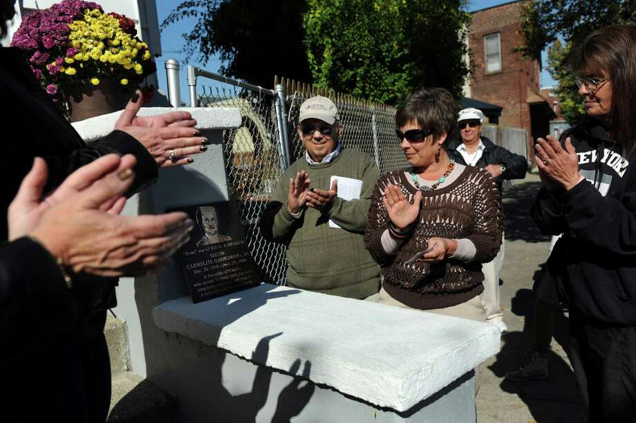 Troy's Little Italy Neighborhood pays tribute to the late Sister Carmelite Germinario as they unveil a bronze plaque at her former residence on Saturday, Oct. 12, 2013, in Troy, N.Y. Joining them are Mike Esposito, chair of the Tribute Committee, left, and Helen Casale, niece of the late sister, center. (Cindy Schultz / Times Union) Photo: Cindy Schultz / 00024145A