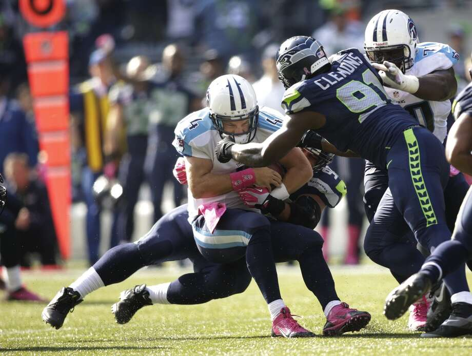 Tennessee Titans quarterback Ryan Fitzpatrick is tackled by defensive tackle Jordan Hill, as Seahawks' Chris Clemons (91) closes in at right, during the first half of an NFL football game, Sunday, Oct. 13, 2013, in Seattle. (AP Photo/Scott Eklund) Photo: AP