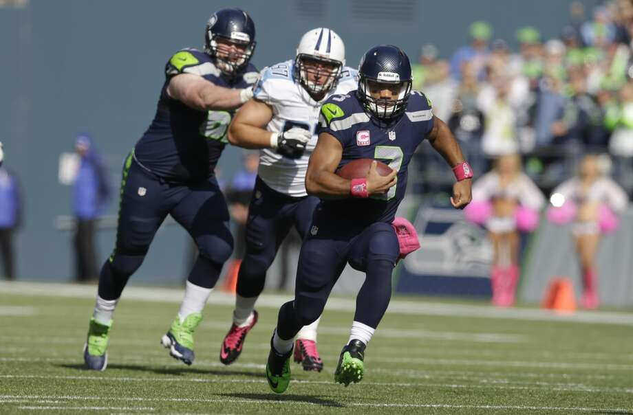 Seattle Seahawks quarterback Russell Wilson, right, runs the ball as Tennessee Titans' Karl Klug, center, and Seahawks' Paul McQuistan, left, pursue during the first half of an NFL football game, Sunday, Oct. 13, 2013, in Seattle. (AP Photo/Elaine Thompson) Photo: ASSOCIATED PRESS