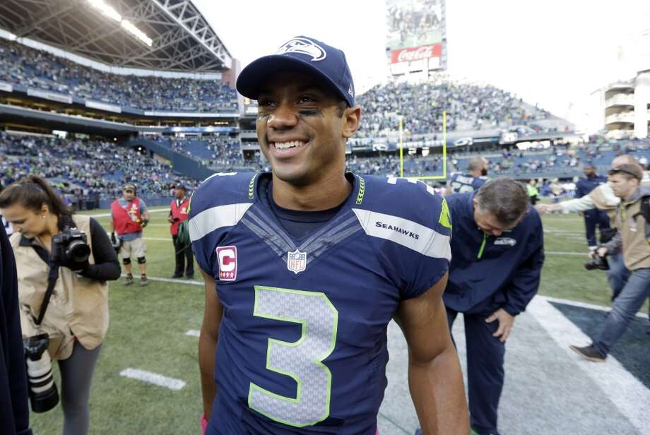 Seattle Seahawks quarterback Russell Wilson smiles as he walks off the field after the Seahawks beat the Tennessee Titans in an NFL football game, Sunday, Oct. 13, 2013, in Seattle. The Seahawks won 20-13. (AP Photo/Elaine Thompson) Photo: AP