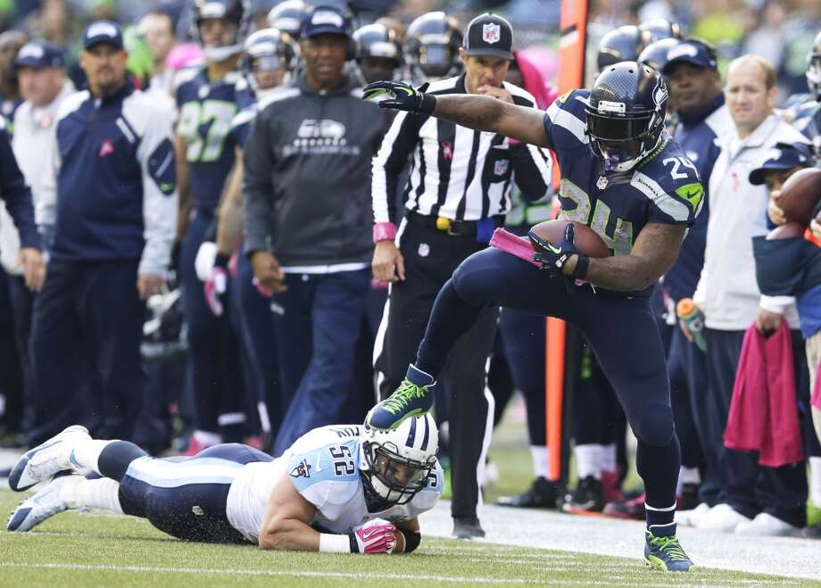 Seattle Seahawks Marshawn Lynch (24) breaks from a tackle attempt by Tennessee Titans' Colin McCarthy in the second half of an NFL football game, Sunday, Oct. 13, 2013, in Seattle. (AP Photo/Elaine Thompson) Photo: AP