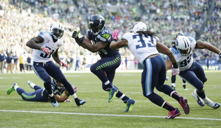 Seattle Seahawks' Marshawn Lynch, center, runs for a touchdown past Tennessee Titans' Michael Griffin (33) and Ropati Pitoitua, right, in the second half of an NFL football game, Sunday, Oct. 13, 2013, in Seattle. (AP Photo/Elaine Thompson) Photo: ASSOCIATED PRESS