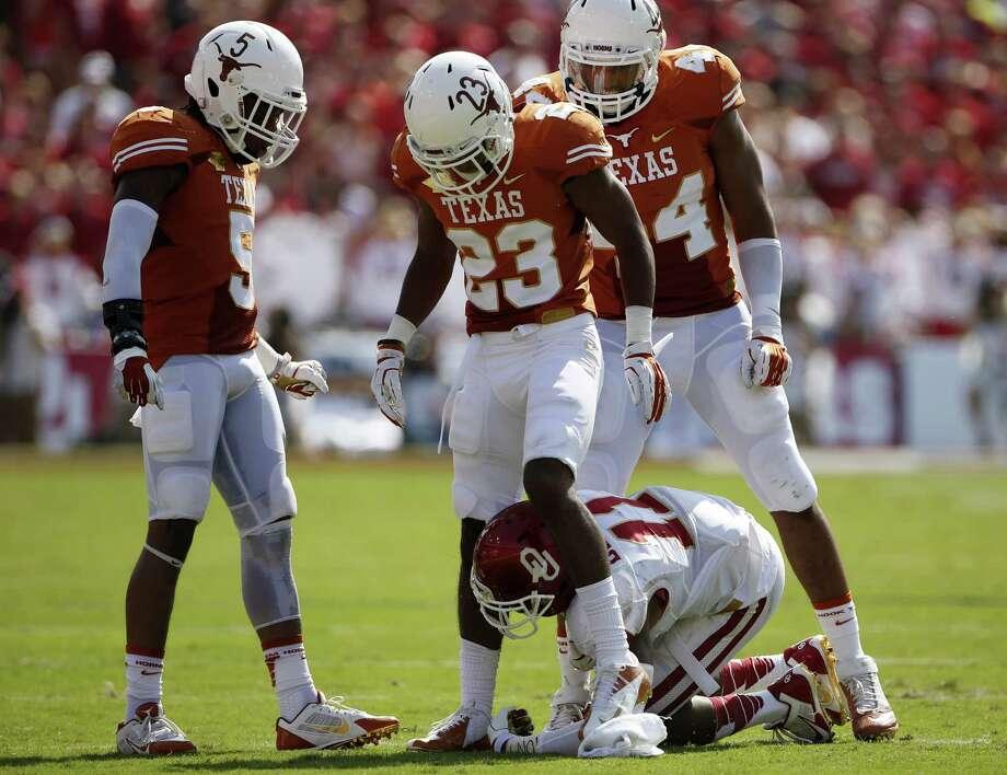 Oklahoma's Lacoltan Bester feels the wrath of a suddenly dominant Texas defense. Photo: Garett Ray Fisbeck, MBR / Dallas Morning News