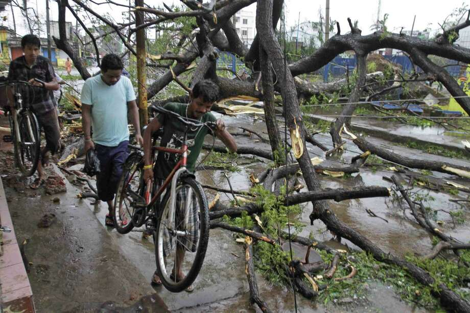 Indian men carry their bicycles past uprooted trees after Cyclone Phailin struck India's eastern coastline Saturday. Photo: Bikas Das, Associated Press