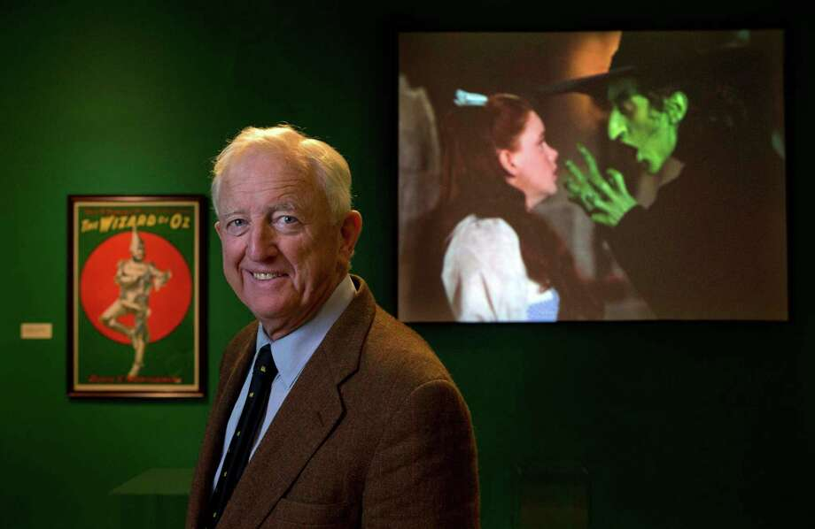 "In this Tuesday, Oct. 8, 2013 photo, Ham Meserve, of Southport, Maine, the son of actress Margaret Hamilton, poses at the Farnsworth Museum, in Rockland, Maine. Hamilton is seen on the screen at right playing the role of the wicked witch of the West in the movie, ""The Wizard of Oz."" The world's largest collection of materials from the movie is being exhibited a few months after the release of a prequel to the original film and the release of the original movie in I-Max format. (AP Photo/Robert F. Bukaty) ORG XMIT: MERB201 Photo: Robert F. Bukaty / AP"