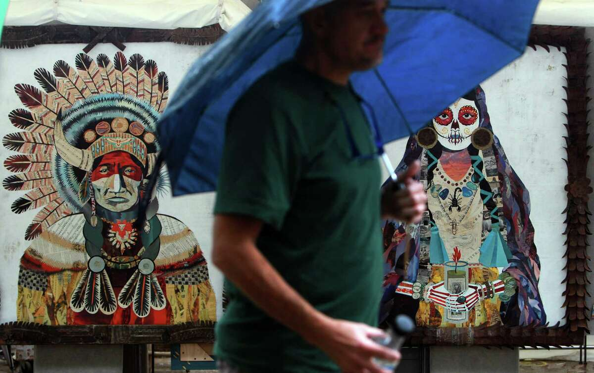 Mixed media pieces by artist Dolan Geiman stay safe despite rain during the last day of the Bayou City Arts Festival on Sunday, Oct. 13, 2013, in Houston.