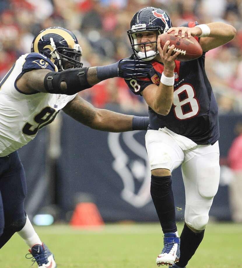 Texans quarterback Matt Schaub tries to avoid being sacked by Rams defensive tackle Michael Brockers. Photo: Karen Warren, Houston Chronicle