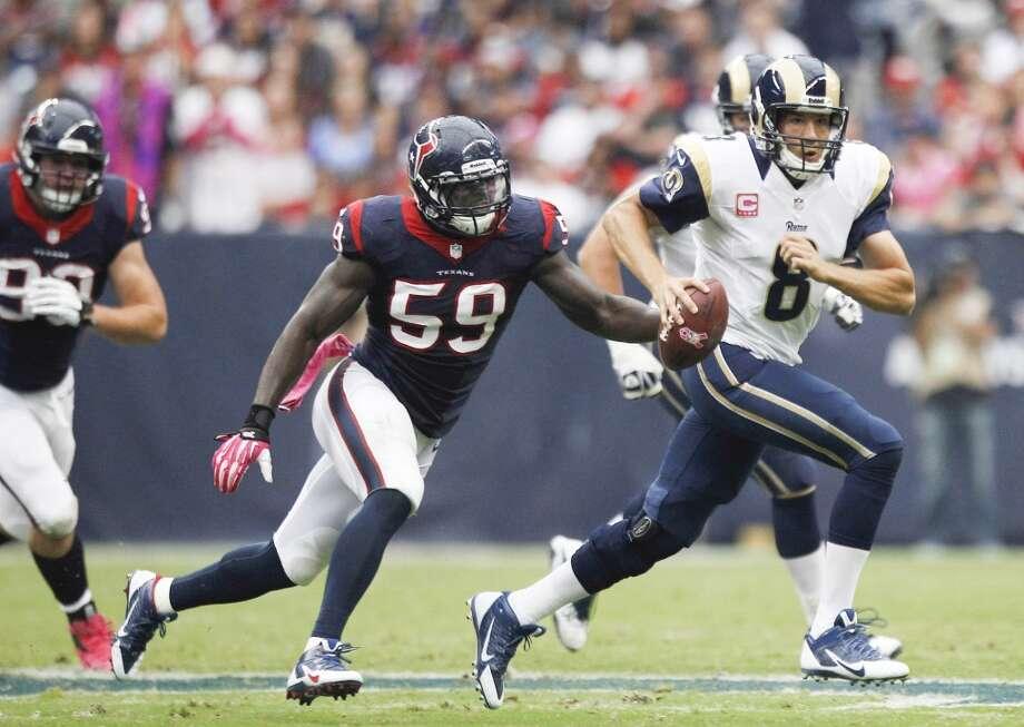 Rams quarterback Sam Bradford scrambles away from Texans outside linebacker Whitney Mercilus. Photo: Brett Coomer, Houston Chronicle