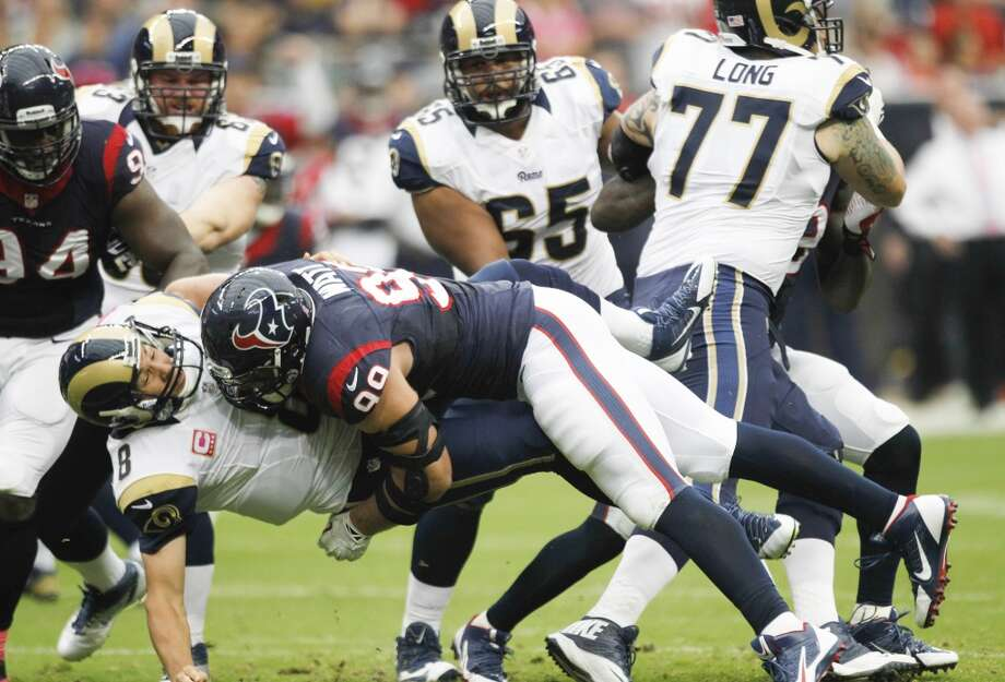 Texans defensive end J.J. Watt hits Rams quarterback Sam Bradford during the first quarter. Photo: Brett Coomer, Houston Chronicle