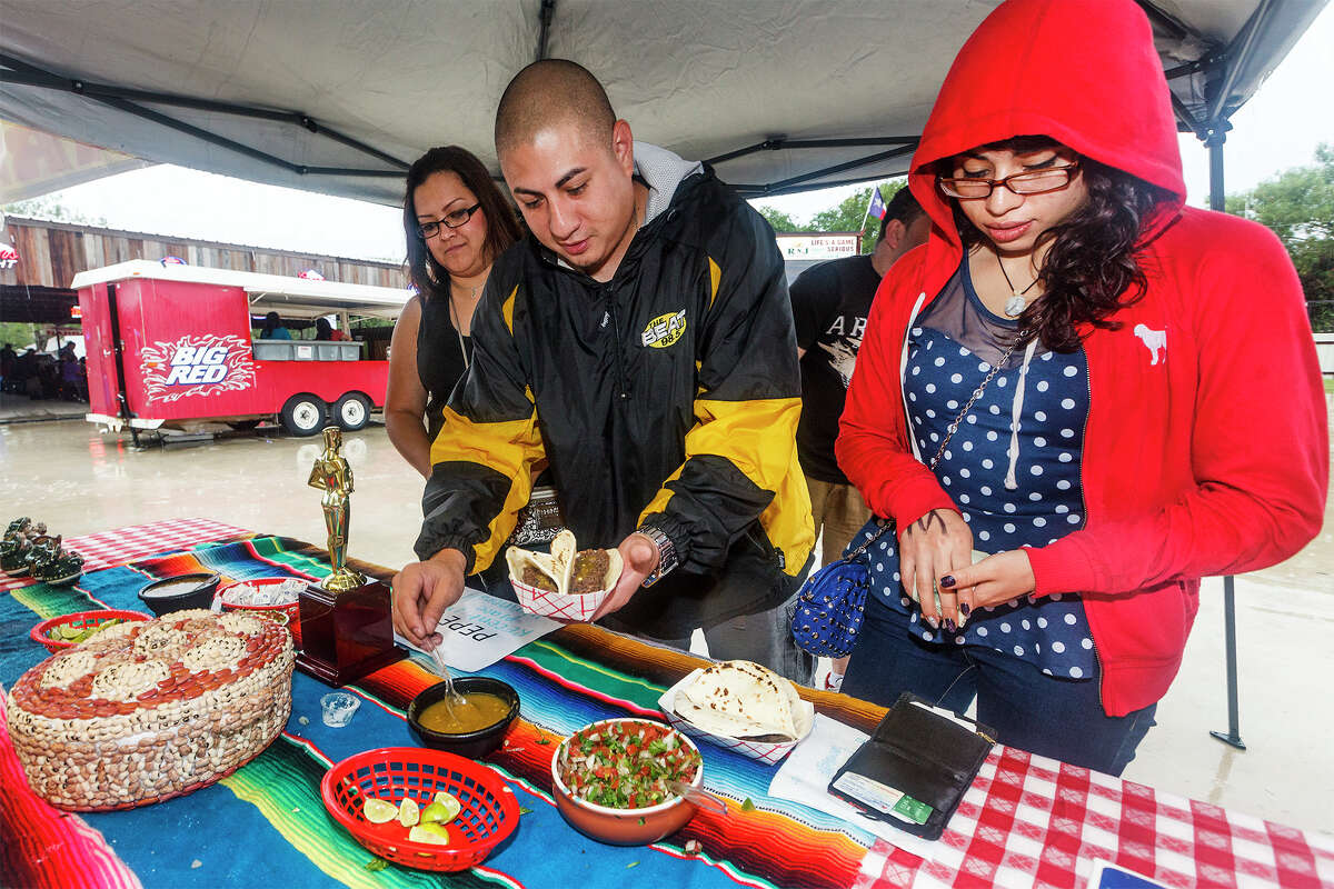 """Ruben """"DJ Quick"""" Mendez (center) gets salsa for his barbacoa tacos with Jennifer Valdez (left) and Amber Mendez at the Barbacoa & Big Red Fall Festival 2013 at the R & J Music Pavilion, 18086 Pleasanton Rd, on Sunday, Oct. 13, 2013. MARVIN PFEIFFER/ mpfeiffer@express-news.net"""