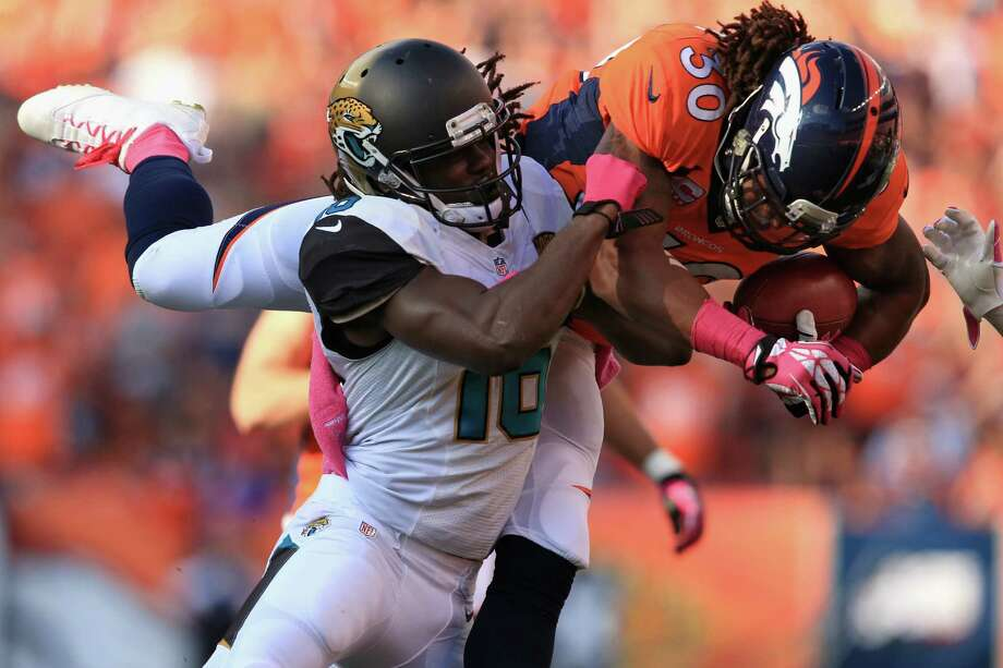 Denver's David Bruton (right) is hit by Jacksonville's Denard Robinson after gaining 35 yards on a fake punt. The Jags (0-6) kept it close most of the way. Photo: Doug Pensinger / Getty Images