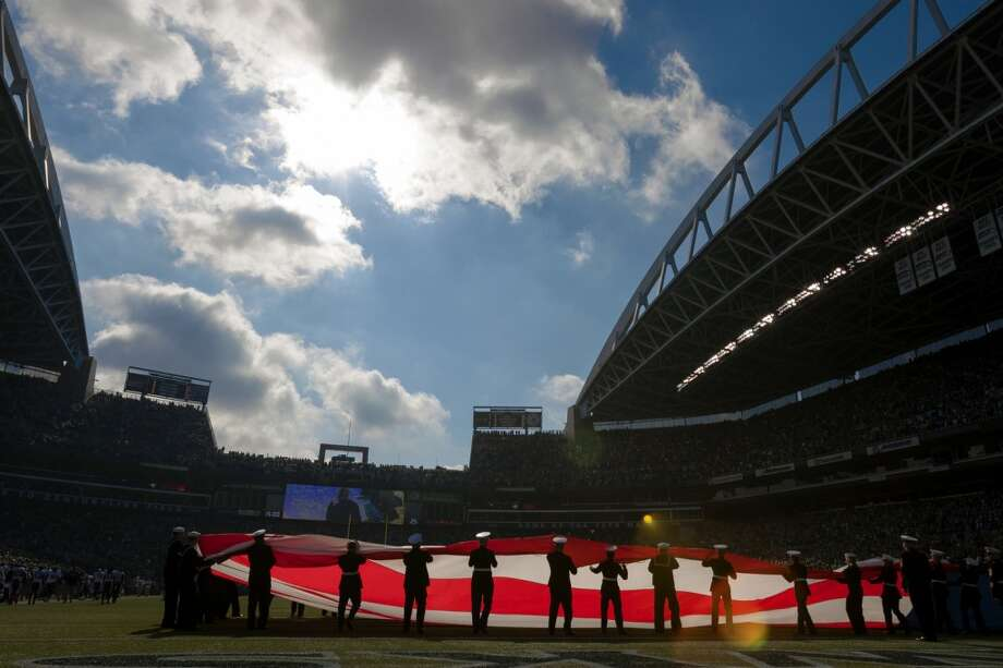 A mix of military personnel hold the flag outstretched before a Seahawks game Sunday, Oct. 13, 2013, at CenturyLink Field in Seattle. (Jordan Stead, seattlepi.com) Photo: JORDAN STEAD, SEATTLEPI.COM