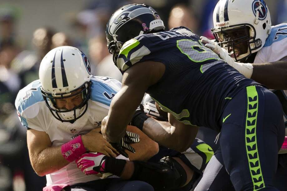 Titan quarterback Ryan Fitzpatrick, left, is sacked by Seahawks during the first half of a game Sunday, Oct. 13, 2013, at CenturyLink Field in Seattle. The Titans led the Seahawks 10-7 at the half. (Jordan Stead, seattlepi.com) Photo: JORDAN STEAD, SEATTLEPI.COM