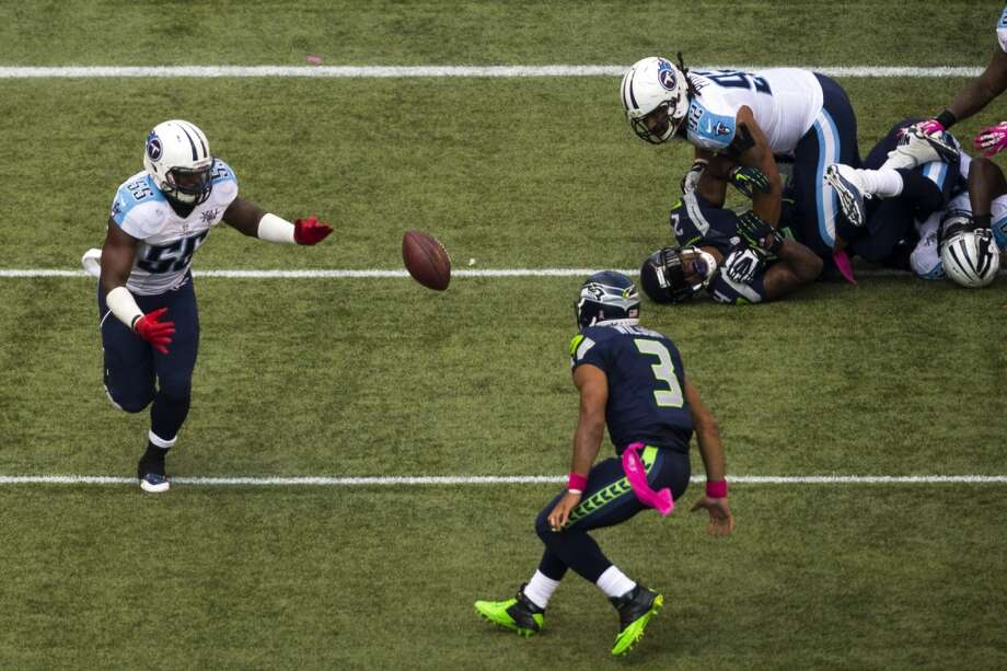 Seattle's Russell Wilson, bottom, prepares to scoop up a fumbled Titans ball after fumbling it first himself during the second half of a Seahawks game against the Tennessee Titans Sunday, Oct. 13, 2013, at CenturyLink Field in Seattle. The Seahawks beat the Titans 20-13. (Jordan Stead, seattlepi.com) Photo: JORDAN STEAD, SEATTLEPI.COM