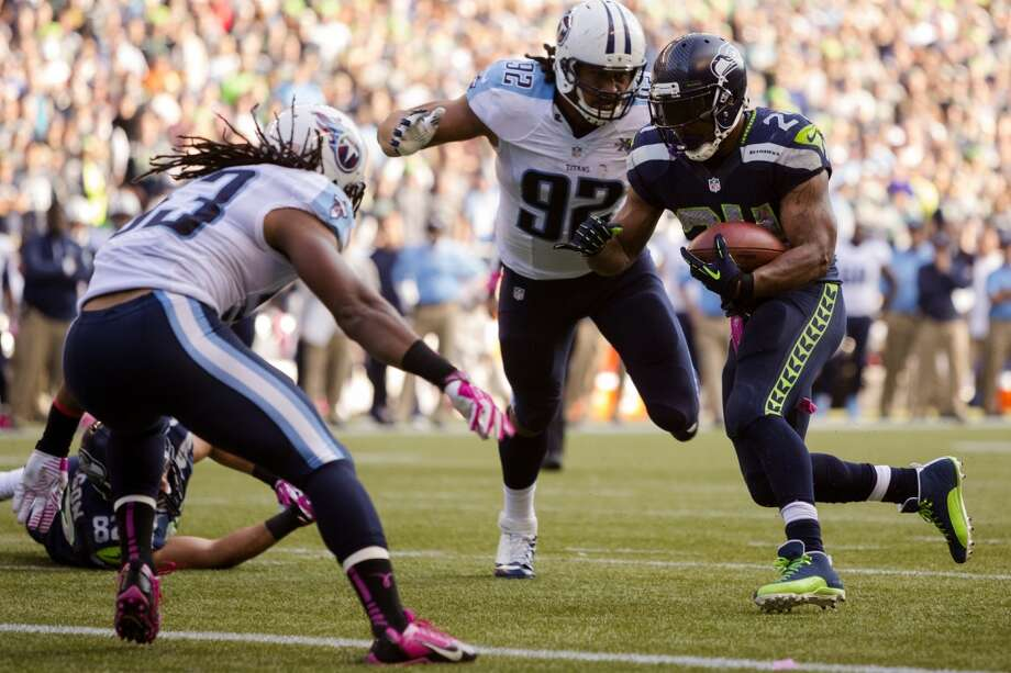 Marshawn Lynch, right, weaves through Tennessee Titan defense to make a touchdown during the second half of a game Sunday, Oct. 13, 2013, at CenturyLink Field in Seattle. The Seahawks beat the Titans 20-13. (Jordan Stead, seattlepi.com) Photo: JORDAN STEAD, SEATTLEPI.COM