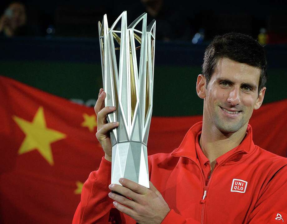 Novak Djokovic of Serbia celebrates with the winners trophy after defeating Juan Martin Del Potro of Argentina during their men's singles final at the Shanghai Masters 1000 tennis tournament held in the Qizhong Tennis Stadium in Shanghai on October 13, 2013.  Djokovic went on to win 61, 3-6, 7-6.                  AFP PHOTO /Mark RALSTONMARK RALSTON/AFP/Getty Images Photo: MARK RALSTON / AFP