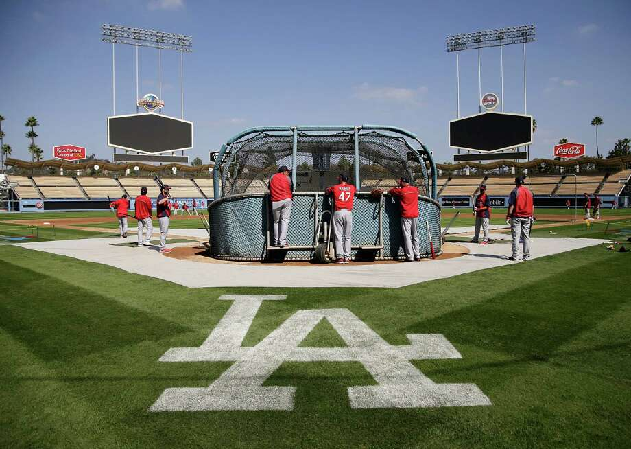 A logo for the Los Angeles Dodgers is painted on the field as the St. Louis Cardinals practice in preparation for Monday's Game 3 of the National League baseball championship series against the Dodgers, on Sunday, Oct. 13, 2013, in Los Angeles. (AP Photo/Jae C. Hong) ORG XMIT: LAD102 Photo: Jae C. Hong / AP