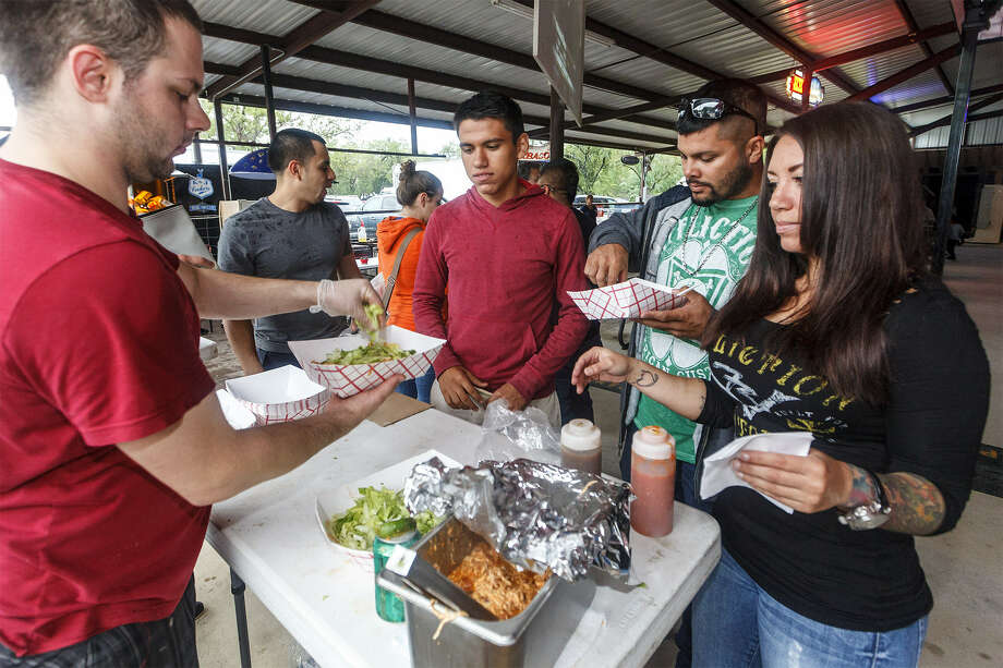 Michael Heinz prepares nachos for (from left) David Castillo, Clarence McFarland and Christina McFarland at the Barbacoa & Big Red Fall Festival at the R&J Music Pavilion in south Bexar County. Photo: Photos By Marvin Pfeiffer / San Antonio Express-News