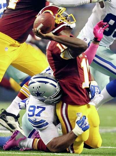 Dallas Cowboys' Jason Hatcher sacks Washington Redskins' Robert Griffin III as he tries to pass duri