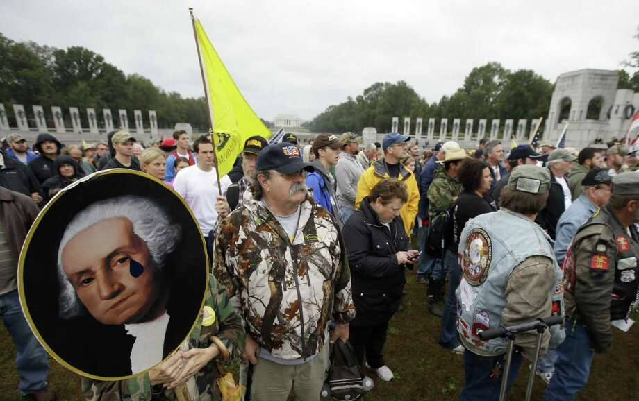Noreen Grimm, holding a George Washington portrait, along with husband David Grimm protests the closing of the U.S. National World War II Memorial because of the government shutdown. Photo: Alex Brandon / Associated Press
