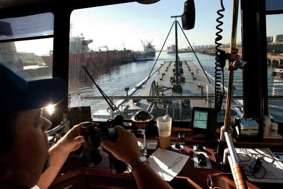 Capt. Eric Pierce, aboard the San Joaquin of Buffalo Marine Services, looks for clearance as he pushes a barge through the Port of Houston on Tuesday.