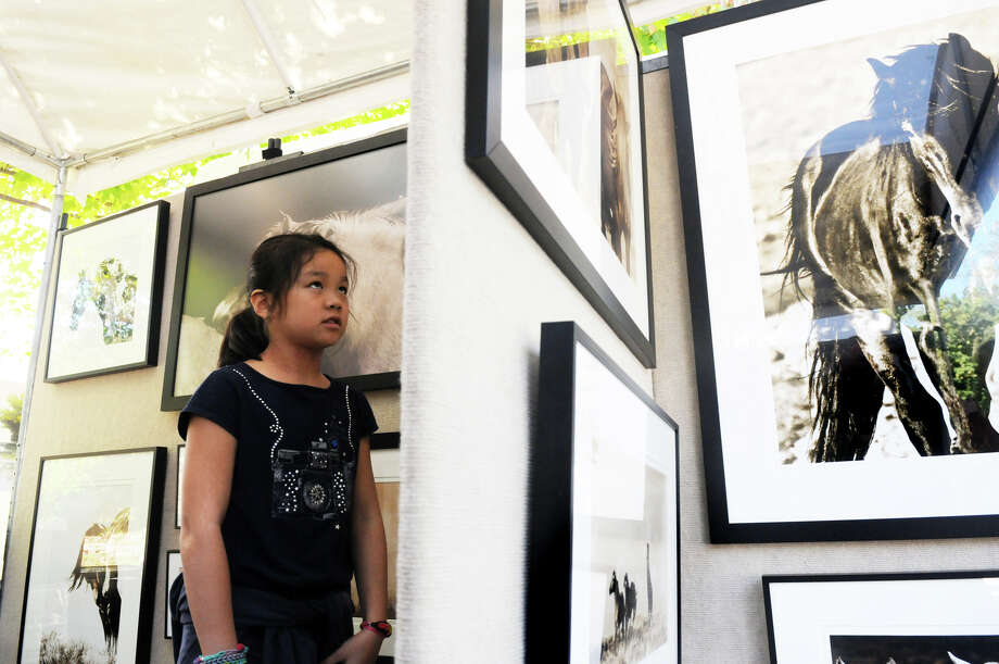 Sabrina Sieh, 10, browses a collection of wild horse photographs taken by artist Caroline Christie at the Bruce Museum's 32nd Annual Outdoor Arts Festival featuring more than 85 artists from all over the country at the Bruce Museum in Greenwich, Conn., Oct. 12, 2013. Photo: Keelin Daly / Stamford Advocate Freelance