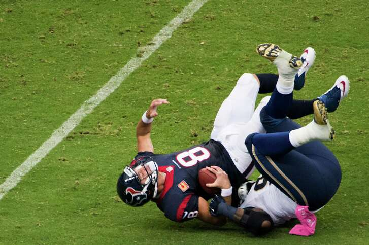 Texans quarterback Matt Schaub (8), who eventually left the game, is sacked by the Rams' Michael Brockers in the first half.