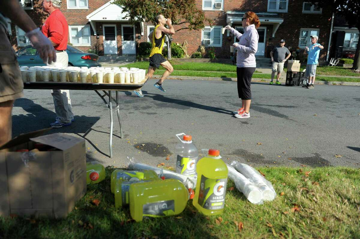 Volunteer Alison Camarota, right, from Latham, hands out cups of Gatorade to runners during the Mohawk Hudson River Marathon on Sunday, Oct. 13, 2013 in Watervliet, NY. The marathon started in Schenectady and ended in Albany. (Paul Buckowski / Times Union)
