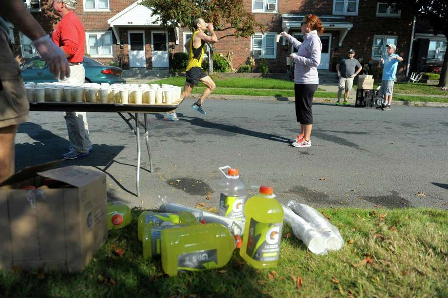 Volunteer Alison Camarota, right, from Latham, hands out cups of Gatorade to runners during the Mohawk Hudson River Marathon on Sunday, Oct. 13, 2013 in Watervliet, NY.  The marathon started in Schenectady and ended in Albany.     (Paul Buckowski / Times Union) Photo: Paul Buckowski / 00024202A