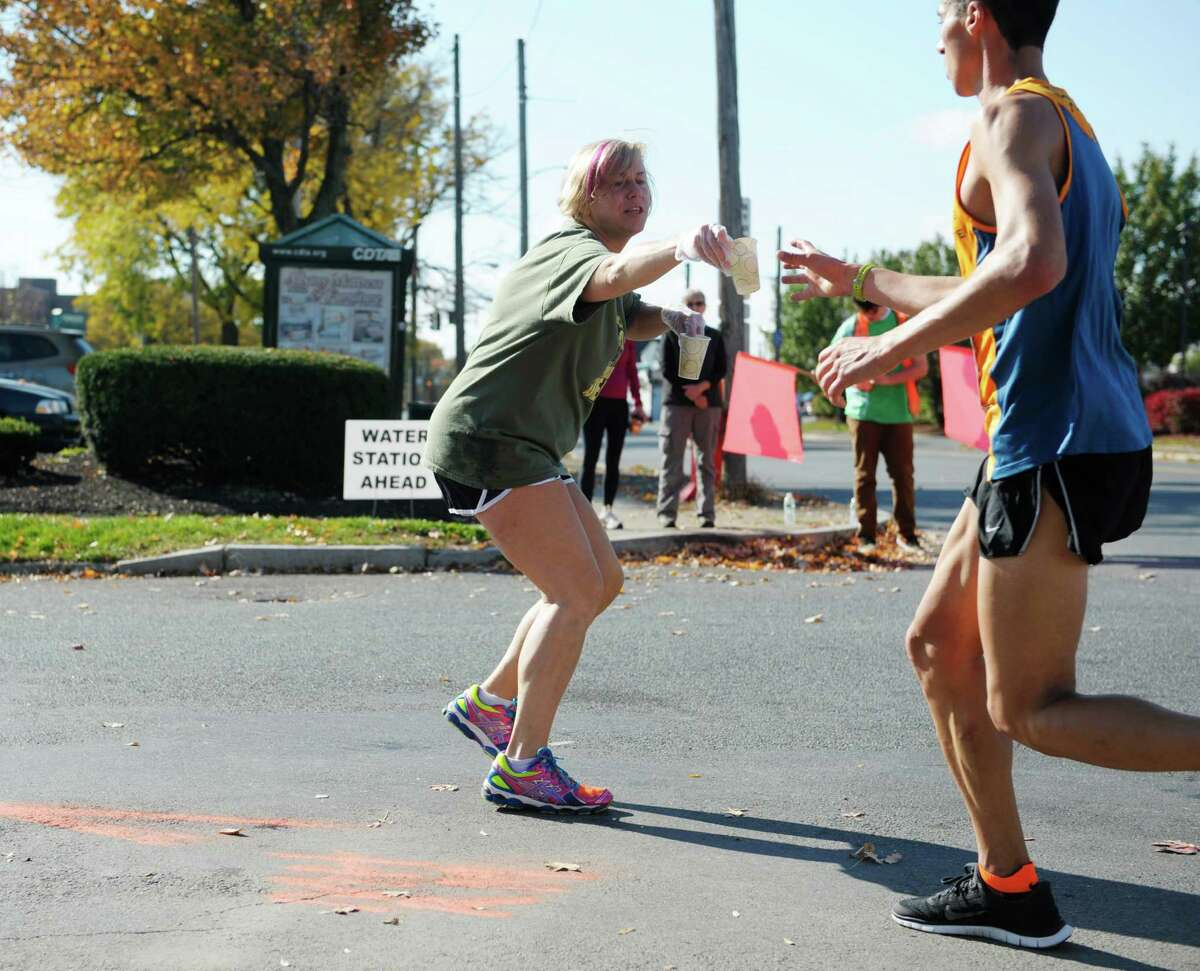 Kristin Griswold, left, from Schaghticoke hands out cups of Gatorade to runners during the Mohawk Hudson River Marathon on Sunday, Oct. 13, 2013 in Watervliet, NY. The marathon started in Schenectady and ended in Albany. (Paul Buckowski / Times Union)