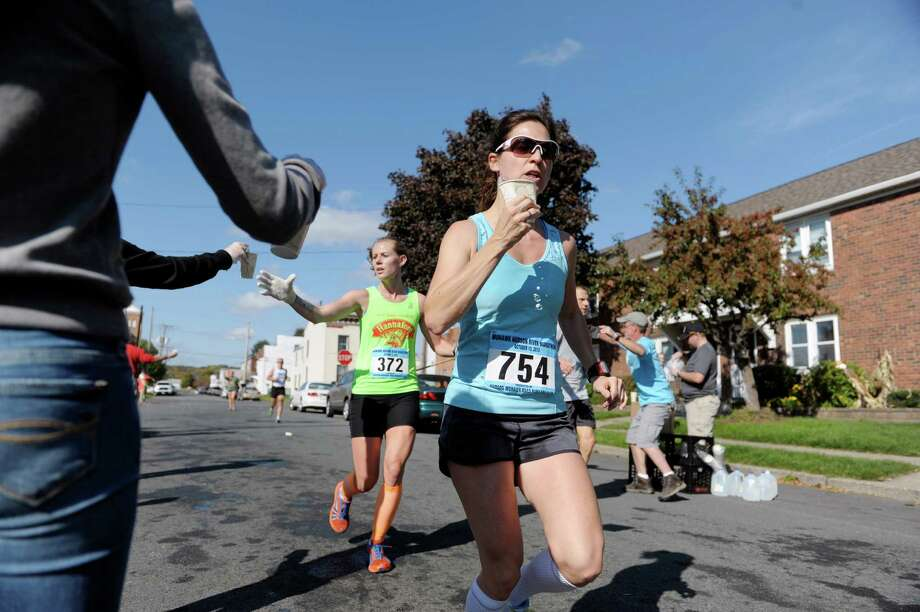 Runners grab cups of water along 21st St.  during the Mohawk Hudson River Marathon on Sunday, Oct. 13, 2013 in Watervliet, NY.  The marathon started in Schenectady and ended in Albany.     (Paul Buckowski / Times Union) Photo: Paul Buckowski / 00024202A