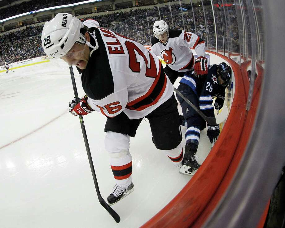 New Jersey Devils' Patrik Elias (26), Anton Volchenkov (28) and Winnipeg Jets' Blake Wheeler (26) fight for the puck during second period NHL hockey action in Winnipeg, Sunday, Oct. 13, 2013. (AP Photo/The Canadian Press, Trevor Hagan) ORG XMIT: WPGT110 Photo: Trevor Hagan / CP