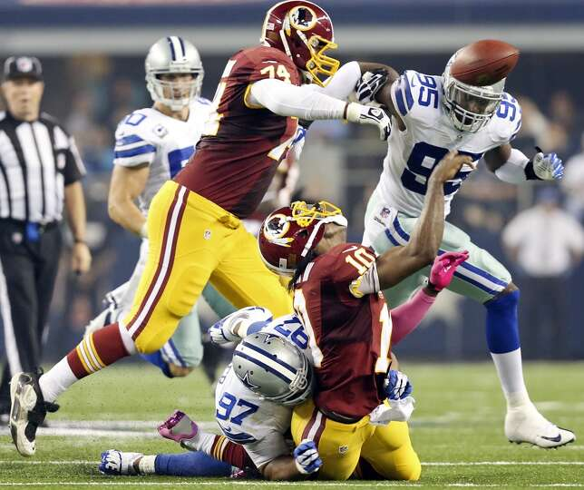 Dallas Cowboys' Jason Hatcher sacks Washington Redskins' Robert Griffin III as he tries to pass duri