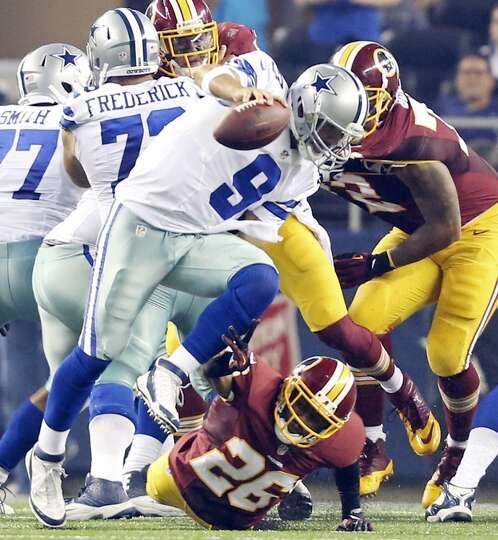 Dallas Cowboys' Tony Romo looks for room around Washington Redskins' Josh Wilson during second half