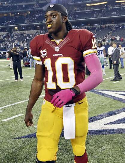 Washington Redskins' Robert Griffin III walks off the field after the game with the Dallas Cowboys d